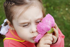 Little girl presses to cheek pink flower Stock Image