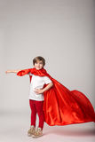 Little girl pretend superwoman in red cape Royalty Free Stock Images