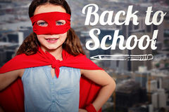 Composite image of little girl pretending to be a superhero. Little girl pretending to be a superhero against towers and building in city Royalty Free Stock Photo