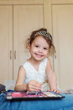 Little girl with princess crown playing with make up Royalty Free Stock Image