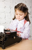 Little girl prints on the ancient typewriter Stock Images