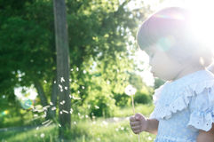 Little girl profile blowing dandelion flower at summer. Child enjoying nature in park Royalty Free Stock Photos