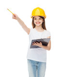 Little girl in protective helmet with clipboard. Construction and people concept - smiling little girl in protective helmet with clipboard pointing finger at Royalty Free Stock Photo
