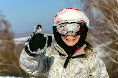 A little girl in a protective helmet and snow mask masked with s. Now, shows her thumb up.The concept of winter fun Stock Image