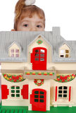 Little girl protruding. Behind toy house Stock Photos