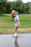 Little girl and the puddle Royalty Free Stock Photo