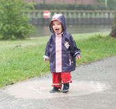 Little girl in a puddle. Loughing little girl in a rain puddle royalty free stock photo