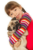 Little girl and the Pug-dog. Isolated on a white background Stock Photography