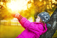 Little girl pulling her hand in autumn park Royalty Free Stock Image