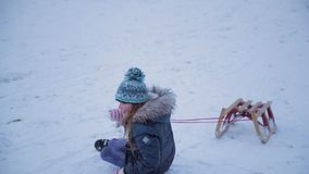 Falling Over in the Snow. Little girl is pulling her sled up a hill and falls over. She starts throwing snowballs at the camera for catching her stock video footage
