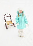 Little girl pulling her sledge in winter day Royalty Free Stock Image