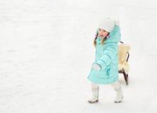 Little girl pulling her sledge in winter day Stock Image