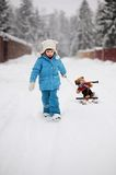 Little girl is pulling her snow scooter with a toy Stock Image