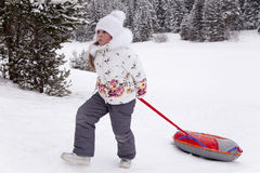 Little girl pulling the strap snow tubing. Royalty Free Stock Photos