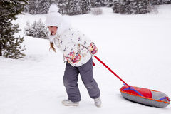 Little girl pulling the strap snow tubing. royalty free stock images