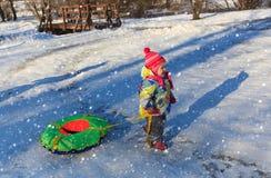 Little girl pulling tube for winter slide Stock Photo