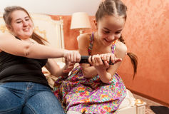 Little girl pulling tv remote out of adult sister Stock Image