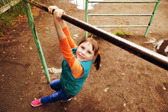 Little girl pulls on the bar. Portrait of a young girl hanging like monkey on the bar at the playground Royalty Free Stock Image