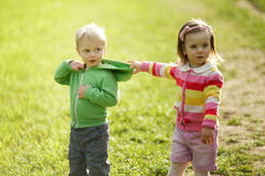 Little girl pulls the boy's hood Royalty Free Stock Image