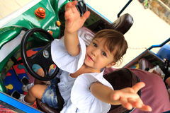 Little girl pulls her arms up while sitting on the driver`s seat of a children`s car Royalty Free Stock Photography