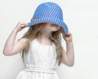 Little girl pulls her hat down over her head. To avoid people Royalty Free Stock Photo