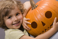Little girl with pumpkin. Girl with jack-o-lantern at halloween time Royalty Free Stock Photo