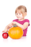 Little girl with pumpkin and apple Stock Photography