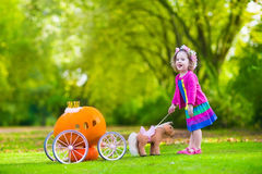 Little girl at pumpkin patch at Halloween. Cute curly little girl playing Cinderella fairy tale holding magic wand next to a pumpkin carriage in autumn park at Royalty Free Stock Photos