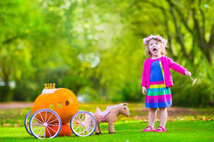 Little girl at pumpkin patch at Halloween. Cute curly little girl playing Cinderella fairy tale holding magic wand next to a pumpkin carriage in autumn park at Stock Photos