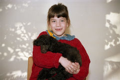 Little Girl and a Puppy. A little girl in a red sweater holing her poodle puppy Stock Photography