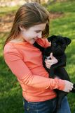 Little girl with puppy. Cute little girl holding black pug puppy Royalty Free Stock Image