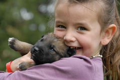 Little girl and puppy. Little girl and her very young puppy purebred belgian shepherd malinois Royalty Free Stock Image