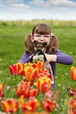 Little girl with puppy pet in tulip garden Royalty Free Stock Photos