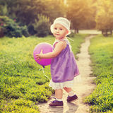 Little girl with a purple balloon Stock Photography