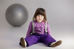 Little girl in purple clothes with big ball for fitness on gray Royalty Free Stock Images
