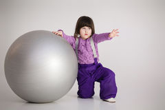 Little girl in purple clothes with big ball for fitness on gray Stock Photo