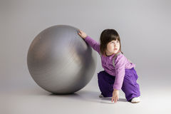 Little girl in purple clothes with big ball for fitness on gray Royalty Free Stock Photo