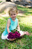 Little girl with purple flowers bouquet on green grass Royalty Free Stock Image