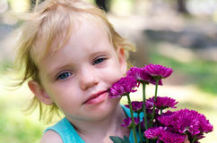Little girl with purple flowers bouquet on green grass Stock Images