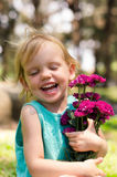 Little girl with purple flowers bouquet on green grass Stock Photos