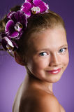 Little girl with purple orchid flowers Royalty Free Stock Photography