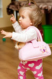 Little girl with purse. Profile shot of a playful little girl with a pink purse on her shoulder, walking and moving her hands expressively Stock Photo