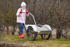 Little girl pushing barrow royalty free stock images