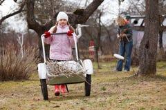 Little girl pushing barrow in gardenne. Little girl pushing barrow in garden, early spring scene Royalty Free Stock Photos