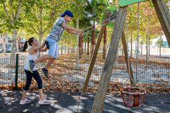 Little girl pushing a child on swing in a park royalty free stock images
