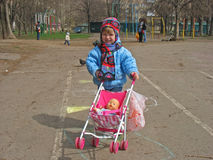 Little Girl Pushing a Dolly in a Pram. Royalty Free Stock Image