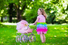 Little girl pushing a toy stoller wth doll Royalty Free Stock Photo