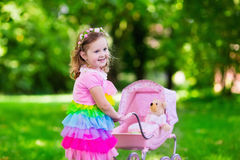 Little girl pushing a toy stoller wth doll Royalty Free Stock Images