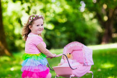 Little girl pushing a toy stoller wth doll Stock Image