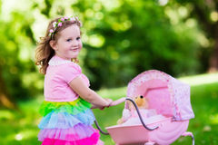 Little girl pushing a toy stoller wth doll Royalty Free Stock Image